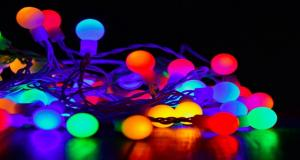 Coloured circular string lights on floor with black background