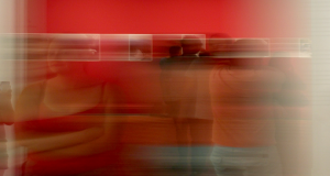 Visitors to exhibition at heritage site with red walls and framed pictures, on time lapse