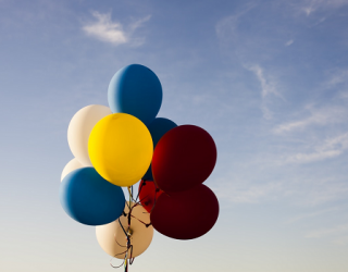Red, yellow, cream and blue balloons in blue sky with clouds