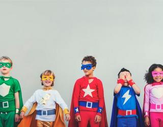 Children standing in a line against a wall, wearing superhero costumes