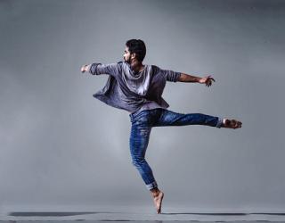 Man dancing in grey room on pointe