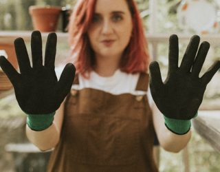 Young woman in brown apron wearing black and green gardening gloves, holding hands up