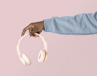 Hand in grey sweatshirt holding pink headphones on pink background