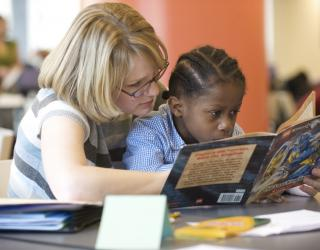 Photo of a woman helping a child to read