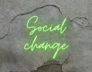 Neon green sign on grey wall saying 'social change'.