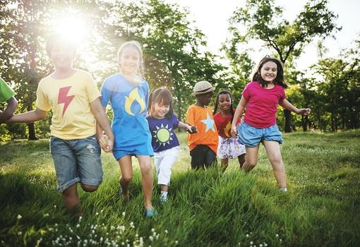 Diverse group of children playing in field with trees
