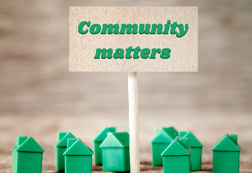 Green plastic houses with signpost reading 'Community matters'