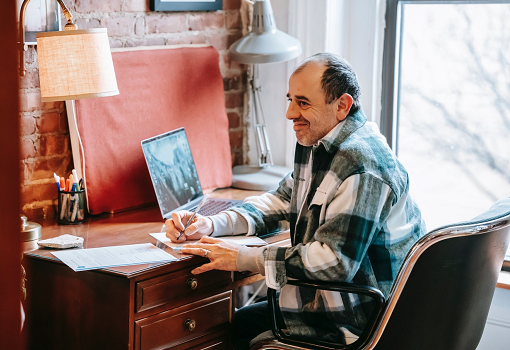 Middle-aged man in check shirt working at laptop on desk, writing notes.