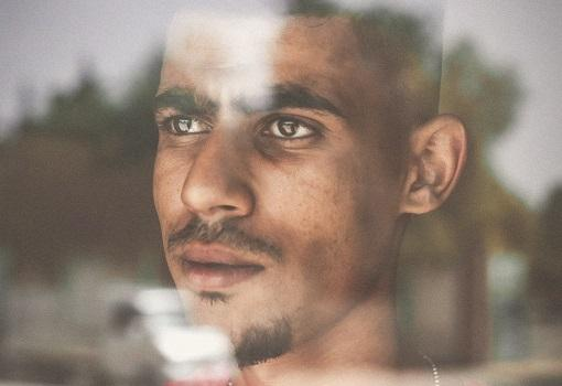 Man looking out of window thinking