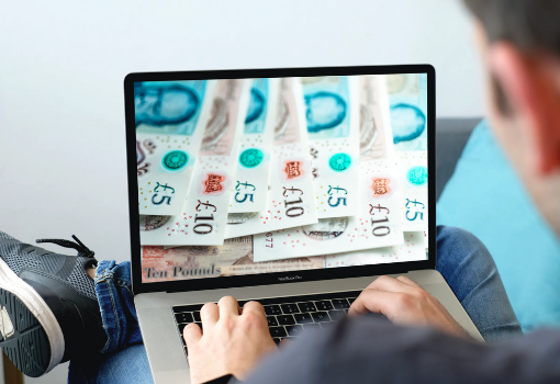 Man looking at laptop screen with £5 and £10 notes