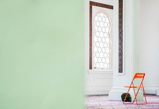 Mosque with mint green walls and orange chair.