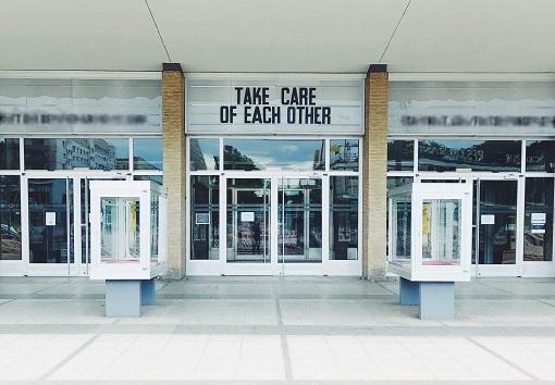 Building with sign above door saying 'Take care of each other'