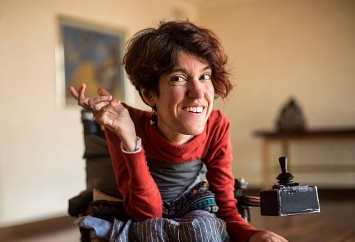 Woman with visible disability raising right hand