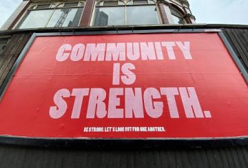 Community is strength word-based poster on fence