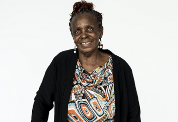 Elderly Black woman in black cardigan with patterned top and earrings