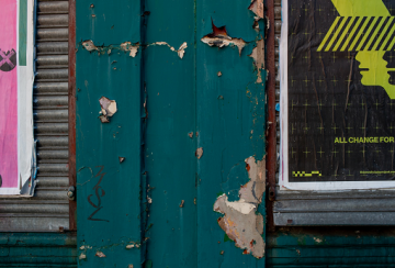 Peeling green paint on wooden panels with posters