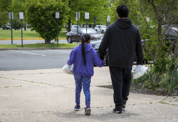 Single father with young daughter in urban street with trees