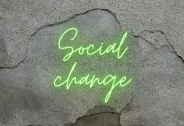 Neon green sign on grey wall saying 'social change'.