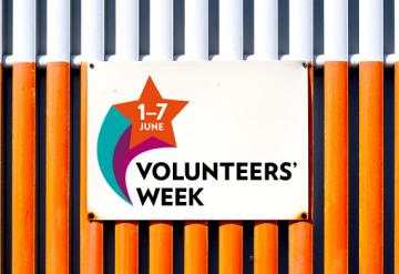 Volunteers' Week sign on white and orange metal background
