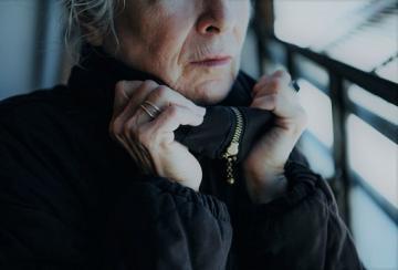 Senior woman in winter coat indoors