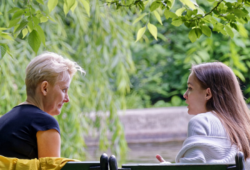 Young person talking to woman on bench next to tree