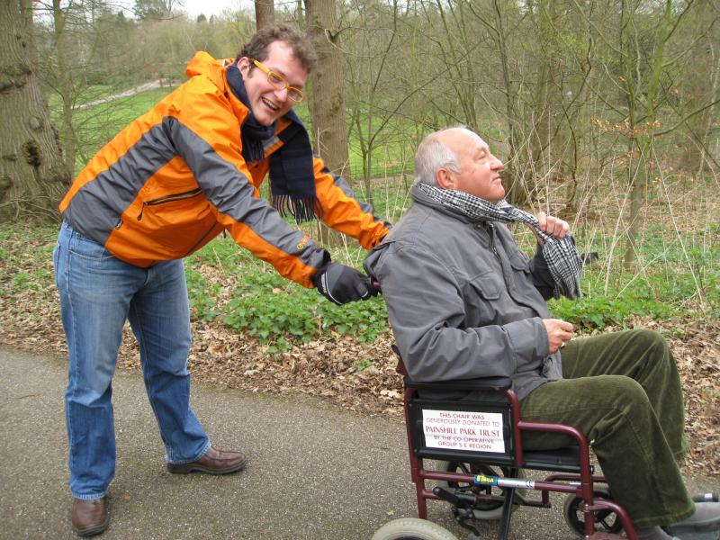 Carer pushing man in wheelchair - both looking happy!