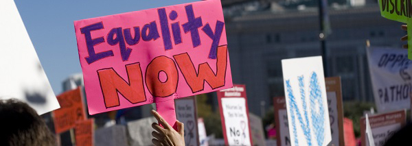 "Photo of woman holding an ""Equality Now"" banner"