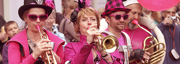 People dressed in hot pink playing the trumpet in Bristol Streets