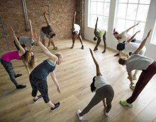 Mixed group yoga class in studio doing warm-up
