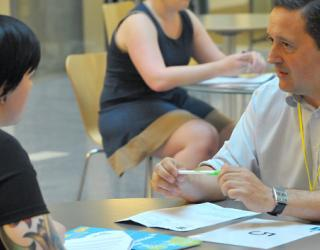 Photo from a previous media trust speed matching event of two people sat chatting at a table.